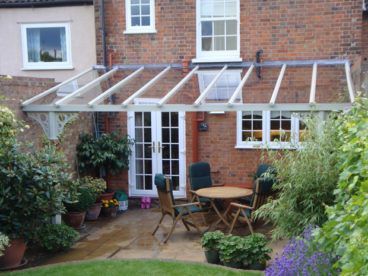 <p>A V8 Verandah in St Albans, with multiple cut-outs for pipework through the laminated glass roof.</p>