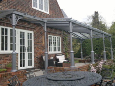 <p>A large and complex V8 Verandah in Surrey, including a hip, glazed gable at either end and differing column heights. Fitted 2013</p>
