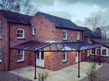 <p>We designed this unusual triangular shaped corner to follow the line of the existing patio on this stunning home in Leicestershire. The verandah provides around 30m2 of covered space, using our simple trumpet columns, with a glass roof and guttering included. Finished in black. </p>